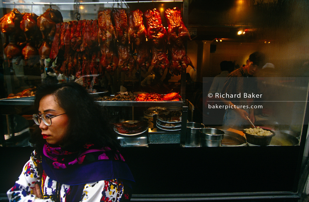 A passer-by stands near to a Chinese restaurant in Gerrard Street in London's Chinatown, England.