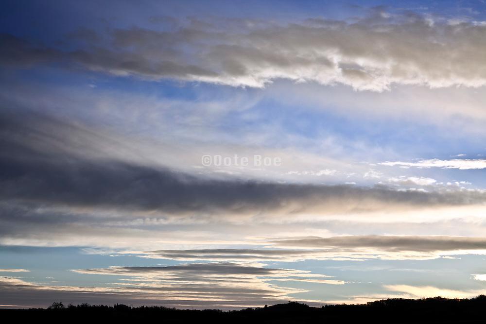 wind swept clouds against blue sky at sunrise