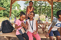 Children playing on their smart phones at the Clarkston Community Center's summer camp. Part of a documentary series on Clarkston, GA.  The most ethnically diverse square mile in America, there are over 70 nationalities that have sought refuge there since the 1980s.
