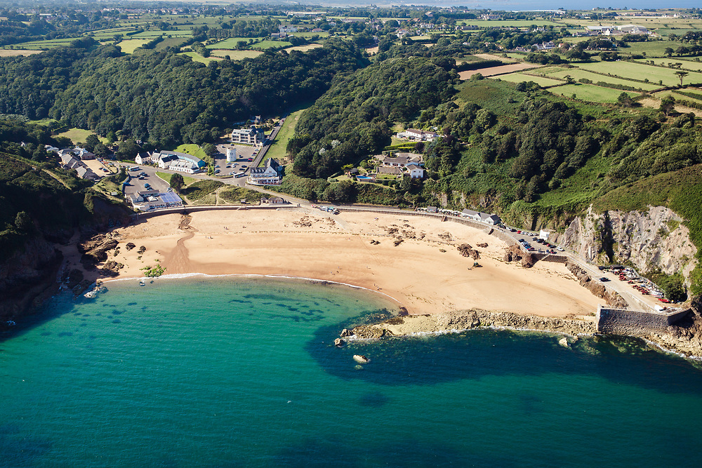 Aerial view of crystal clear turquoise water at Greve de L'Ecq beach on a calm sunny day in Jersey, Channel Islands