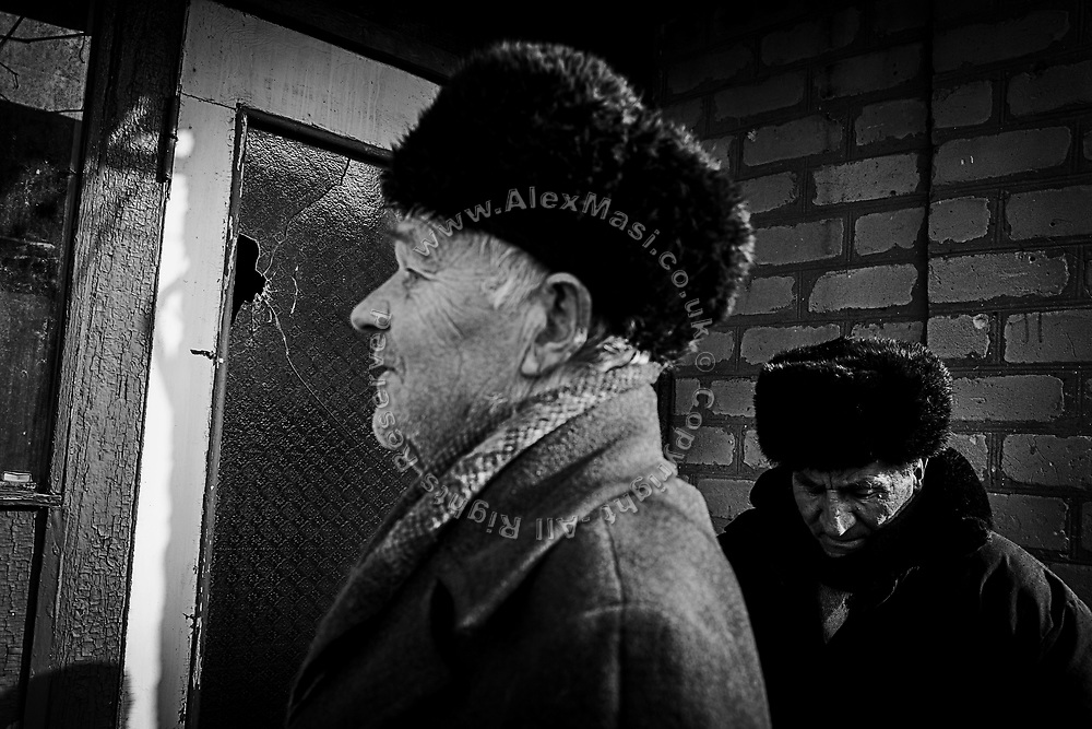 Vasilevich Kopylov, 75, (left) is standing next to his broken door with one of his neighbours, in the frontline town of Avdiivka, where he resides alone in eastern Ukraine.