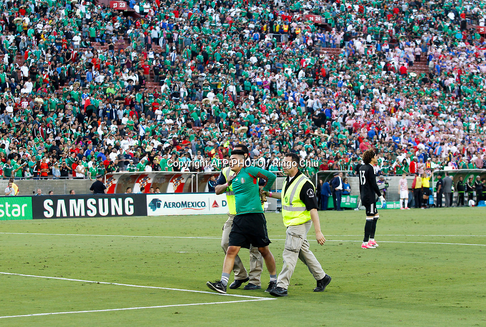Security staff seize a fan who ran onto the field during the second half of an international friendly soccer game between Mexico and Croatia at LA Memorial Coliseum on May 27, 2017 in Los Angeles, California. Croatia won 2-1.  AFP PHOTO / Ringo Chiu