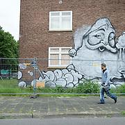 Nederland Den Haag 4 juni 2009 20090604 Foto: David Rozing .Man passeert graffiti op sloopwoning, complex aan Middachtenweg Den Haag Zuidwest ..Foto: David Rozing