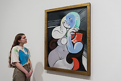 "© Licensed to London News Pictures. 06/03/2018. LONDON, UK. A staff member views ""Nude Woman in a Red Chair (Femme nue dans a fauteuil rouge"", 1932, by Pablo Picasso. Preview of ""Picasso 1932 - Love, Fame, Tragedy"", the Tate Modern's first ever solo exhibition of the work of Pablo Picasso.   More than 100 paintings, sculptures and works on paper covering the year 1932, a pivotal time in Picasso's life, are on display 8 March to 9 September 2018.  Photo credit: Stephen Chung/LNP"