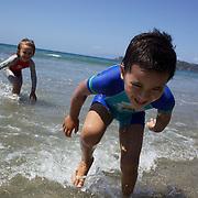 Children play at the waters edge at Onetangi Beach, Waiheke Island, Auckland New Zealand,  2010 Photo Tim Clayton.