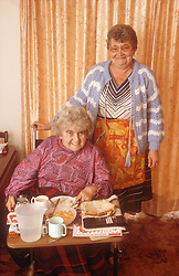 Carer with elderly woman; who is wheelchair user; having breakfast,