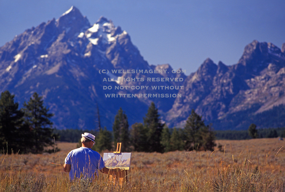 Image of a man painting Mt. Teton and its landscape at Grand Teton National Park, Wyoming, Pacific Northwest by Randy Wells