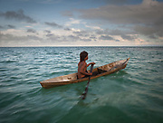 Solpan returning to his stilt house on his duggout canoe after fishing early morning.
