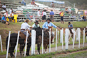 Brazilian Gauchos cowboys males, on their horses talking and preparing to compete in a Rodeo, crowd in background. Gaucho cowboy Rodeo, Flores de Cunha, Rio Grande do Sul.