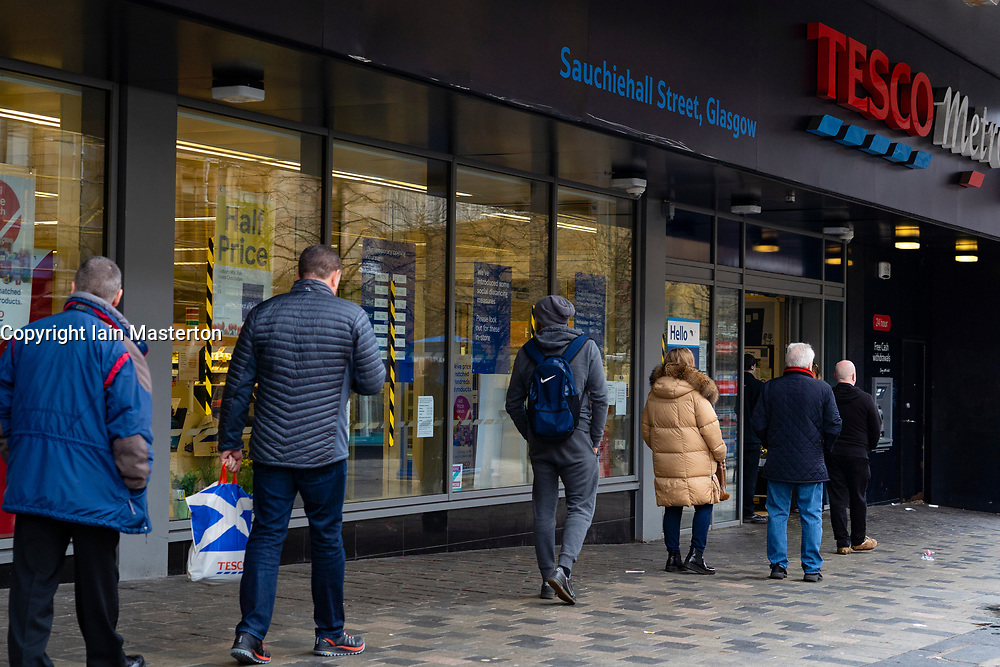 Glasgow, Scotland, UK. 26 March, 2020. Views from city centre in Glasgow on Thursday during the third day of the Government sanctioned Covid-19 lockdown. The city is largely deserted. Only food and convenience stores open. Pictured; Customers queue using social distancing to enter Tesco Metro  supermarket on a one in one out basis. Iain Masterton/Alamy Live News
