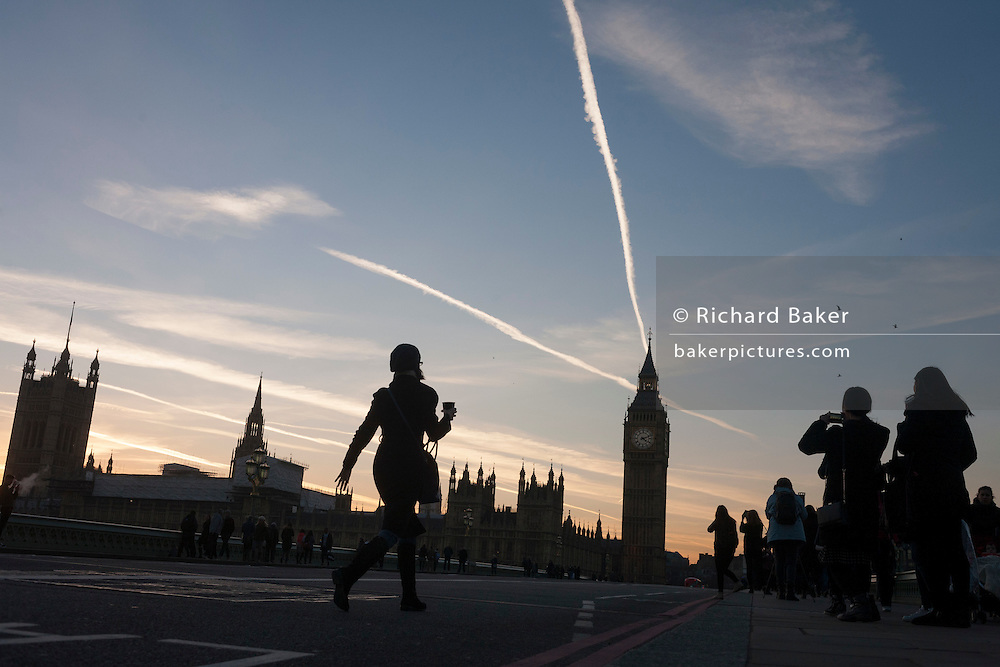 Carrying a drink, a Londoner walks across Westminster Bridge towards tourists taking photos of Britain's parliament, on 17th January 2017, in London England.