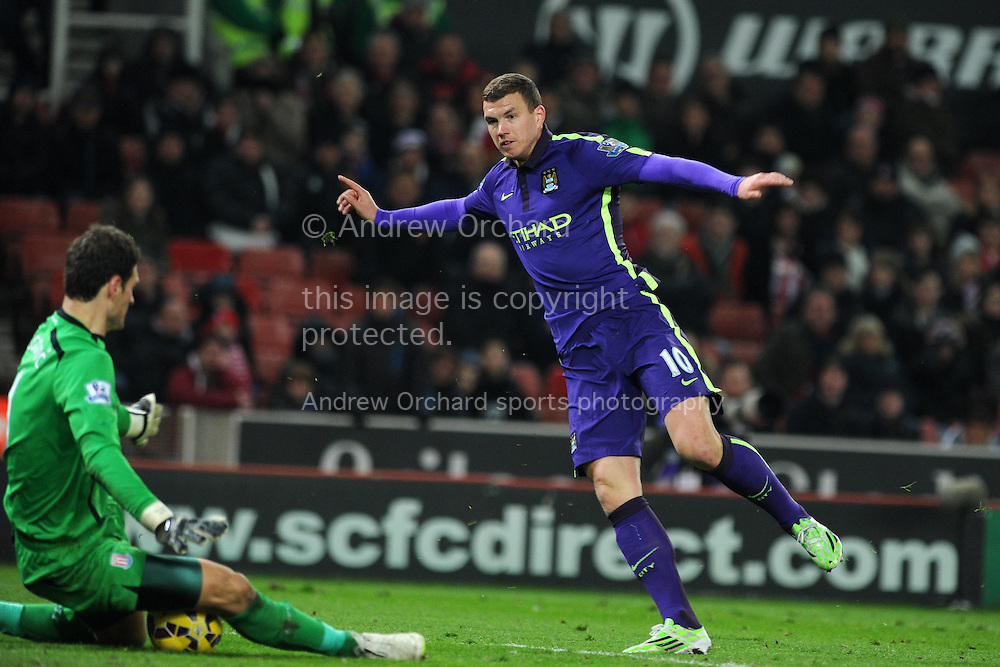 Edin Dzeko  of Manchester city has a shot at goal blocked by Stoke city goalkeeper Asmir Begovic. .Barclays Premier League match, Stoke city v Manchester city at the Britannia Stadium in Stoke on Trent , Staffs on Wed 11th Feb 2015.<br /> pic by Andrew Orchard, Andrew Orchard sports photography.