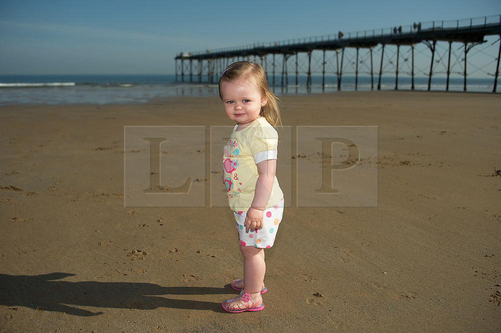 © Licensed to London News Pictures. 28/03/2012..Saltburn, England..As temperatures rise this week the beach at Saltburn in Cleveland attracts the visitors as they enjoy the warm weather.  Polly Wells, 18 months, from Middlesbrough enjoys playing on the beach...Photo credit : Ian Forsyth/LNP