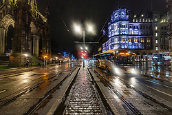 Edinburgh, Scotland, UK. 19 December 2020.  Views of streets and shops in Edinburgh City Centre on evening that Scottish Government announced the highest level 4 lockdown will be enforced from Boxing Day in Scotland.  Pic; Princes Street is very quiet at night in the rain. Iain Masterton/Alamy Live News