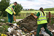 Council refuse collectors clean up a local Derbyshire fly tipping site.  Fly tipping is the illegal dumping of refuse and has become a major problem in the U.K.  Many local Councils have specialist teams that investigate incidents with a view to bringing criminal prosecutions against serious offenders.