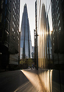 A jogger stretches at More London Place in front of the Shard building at 6pm on 9th April 2020 in London, United Kingdom. Normally crowded with people leaving work the City of London is like a ghost town as workers stay home during the Coronavirus pandemic.