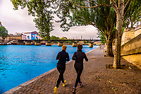 Women jogging on the banks of the Seine River (with Pont des Arts behind), Paris, France.
