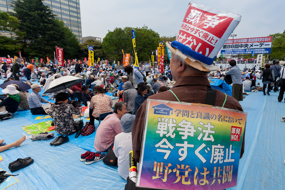 A man wearing a sign against war joins thousands of people at the 88th May Day rally in Central Tokyo to mark International Workers` Day. Tokyo, Japan. Monday, May 1st 2017 The rally started at 9am in Yoyogi Park near Shibuya and the march began at 12:30 despite heavy rain and thunderstorms. The rally called for an end to overwork in Japan along with other labour issues and  protested traditional left wing subjects such as nuclear power and weapons, and Prime Minister Shinzo Abe's plans to reinterpret  Article 9 of the Japanese constitution, thus making the Japanese military Self Defence Force able to fight wars alongside its allies.