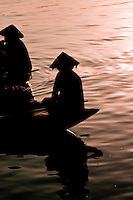 Two women wearing conical hats silhouetted on the Thu Bon river in Hoi An at sunrise.