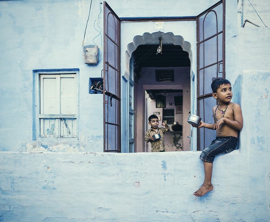 Two boys in front of blue house in the city of Bikaner Rajasthan India. It was once the capital of the princely state of Bikaner. It was founded by founded by Rao Bika in 1486. It is now the fourth biggest city in Rajasthan and although not receiving as many tourists as other cities in the state it is slowly gaining popularity because of the beautiful havelis (houses) an amazing fort and slanderous palaces.