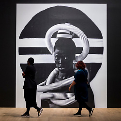 "© Licensed to London News Pictures. 03/11/2020. LONDON, UK. Staff members view a self-portrait ""Sebenzile, Parktown"", 2016, by Zanele Muholi. Preview of the first major UK exhibition by South African visual activist Zanele Muholi at Tate Modern.  260 photographs document black lesbian, gay, trans, queer and intersex lives in South Africa.  The show runs 5 November to 7 March 2021, but will be interrupted by England's coronavirus pandemic lockdown currently due to last 5 November to 2 December.   Photo credit: Stephen Chung/LNP"
