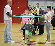 Middletown, New York - A girls goes under the foam bar during a limbo contest at Family Night at the Middletown YMCA on April 2, 2011.