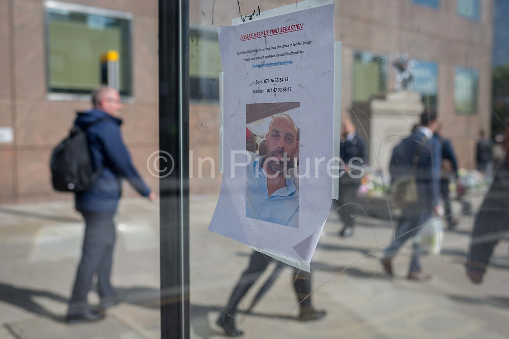 Three days after the terrorist attack in which 7 people died and many others suffered life-changing injuries on London Bridge and Borough Market, the face on a still-missing French citizen Sebastien Belanger appears on a poster at the bus stop near a flower shrine, on 6th June 2017, on London Bridge, in the south London borough of Southwark, England. City commuters now back at work walk respectfully and quietly past the floral memorial at the plinth marking the southern boundary of the City of London, the capitals financial district.
