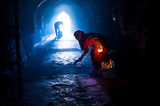 """26th November 2015, New Delhi, India.  A woman sweeps the floor in the ruins of Feroz Shah Kotla in New Delhi, India on the 26th November 2015<br /> <br /> PHOTOGRAPH BY AND COPYRIGHT OF SIMON DE TREY-WHITE a photographer in delhi<br /> + 91 98103 99809. Email: simon@simondetreywhite.com<br /> <br /> People have been coming to Firoz Shah Kotla to pray to and leave written notes and offerings for Djinns in the hopes of getting wishes granted since the late 1970's. Jinn, jann or djinn are supernatural creatures in Islamic mythology as well as pre-Islamic Arabian mythology. They are mentioned frequently in the Quran  and other Islamic texts and inhabit an unseen world called Djinnestan. In Islamic theology jinn are said to be creatures with free will, made from smokeless fire by Allah as humans were made of clay, among other things. According to the Quran, jinn have free will, and Iblīs abused this freedom in front of Allah by refusing to bow to Adam when Allah ordered angels and jinn to do so. For disobeying Allah, Iblīs was expelled from Paradise and called """"Shayṭān"""" (Satan).They are usually invisible to humans, but humans do appear clearly to jinn, as they can possess them. Like humans, jinn will also be judged on the Day of Judgment and will be sent to Paradise or Hell according to their deeds. Feroz Shah Tughlaq (r. 1351–88), the Sultan of Delhi, established the fortified city of Ferozabad in 1354, as the new capital of the Delhi Sultanate, and included in it the site of the present Feroz Shah Kotla. Kotla literally means fortress or citadel."""