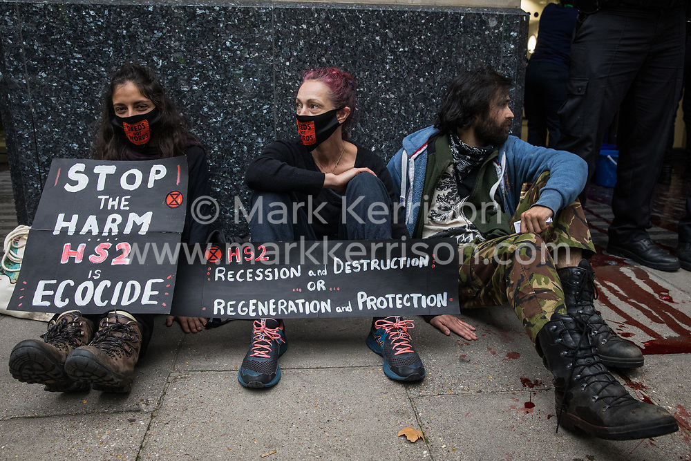 Activists from HS2 Rebellion, an umbrella campaign group comprising longstanding campaigners against the HS2 high-speed rail link as well as Extinction Rebellion activists, are pictured glued to the pavement outside the Department for Transport during a protest on 4 September 2020 in London, United Kingdom. Activists glued themselves to the doors and pavement outside the building and sprayed fake blood around the entrance during a protest which coincided with an announcement by HS2 Ltd that construction of the controversial £106bn high-speed rail link will now commence.