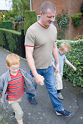 Father and sons walking down the street,