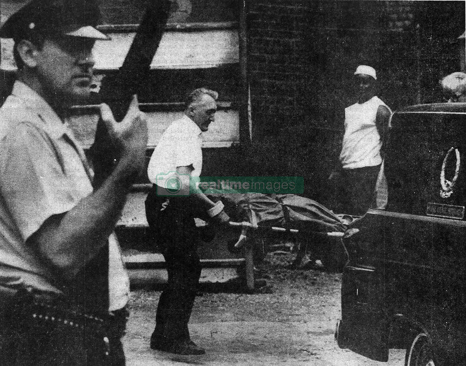 June 20, 2017 - Michigan, U.S. - While a policeman stands guard, the body of an unidentfied msn is removed from the burned out ruins of as building on Seward and Twelfth in the riot area in Detroit in 1967. Another man, also unidentified, was found dead in the rubble. The cause of their death ha not yet been officially determined. (Credit Image: © Detroit Free Press via ZUMA Wire)