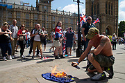 A supporter of Tommy Robinson real mame Stephen Yaxley - Lennon burns the EU flag outside the Houses of Parliament after he was sentenced  to nine months in prison for contempt of court. He was found guilty of filming defendants accused of child sex offences outside Leeds Crown Court and live-streaming the footage on Facebook Live in May, 2018.