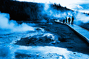 Old Faitful Basin Yellowstone Boardwalk with blue duotone. Steam surrounds people's silhouettes on the board walk the mist comes out of the ground.