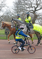 © Licensed to London News Pictures 08/01/2021.         Greenwich, UK. A lady on a bike cycling past police on horseback. Mounted Metropolitan police officers on patrol in Greenwich park in London during a third national Covid lockdown. Photo credit:Grant Falvey/LNP