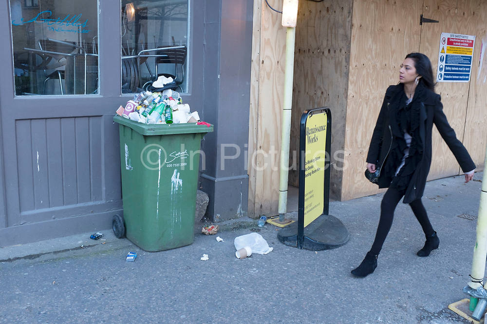 Woman passes a trash filled bin on Bermondsey Street in Southwark, London, UK. This street is a very gentrified and trendy stylish area.