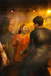 Nepalese teeangers dance in a nightclub in Katmandu, seemingly unaware of the brutal conflict that lies just outside the city in Nepal March 5, 2005. (Ami Vitale)
