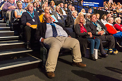 © Licensed to London News Pictures. 29/09/2019. Manchester, UK. A man falls asleep during James Cleverly's speech on first day of the Conservative Party Conference at Manchester Central in Manchester. Photo credit: Andrew McCaren/LNP