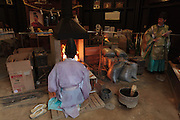 Shinto priests working at a forge in the Kanayama Shrine during he Kanamara festival for the steel phallus in Kawasaki Daishi, Kanagawa, Japan. Sunday April 5th 2015. The Kanamara penis festival celebrates a legend about the defeat of a penis-eating demon. It is a wildly popular festival attracting large numbers of locals and foreigners.
