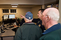 Lieutenant James Leach gives Allan Whitney and Don Bilodeau a tour of the Dispatch Room at Gilford Police Department during the Open House held Thursday evening.  (Karen Bobotas/for the Laconia Daily Sun)