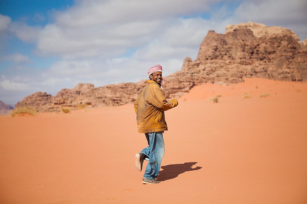 Sudanese Bedouin driver Ahmed runs up a sand dune for fun in Wadi Rum, Jordan.