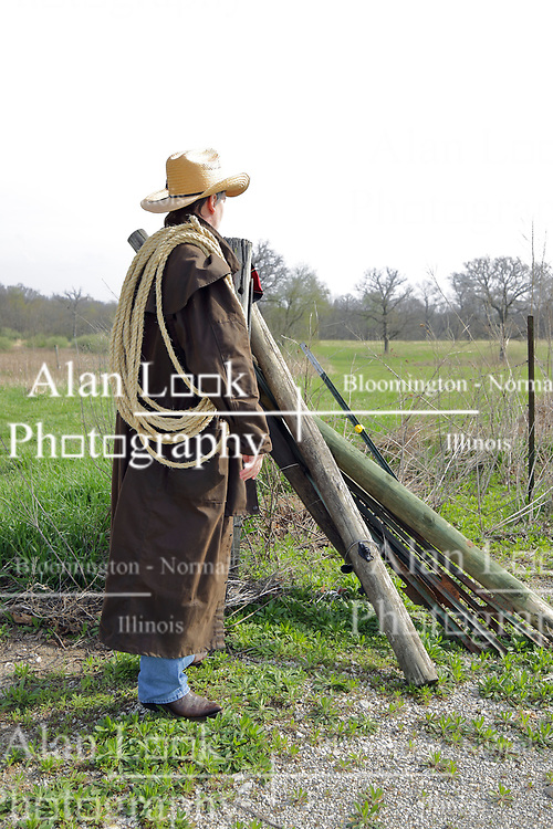 An aging man dressed in western fashions looks the part of a cowboy from days gone by in the American Old West. Accessories include a cowboy hat, boots, denim, sisal rope, western style belt, 12 gauge side by side double barrel shotgun, western duster and a saddle blanket on the fence in the background. Wood and Steel fence posts are stacked together with the spares leaning against strands of barbed wire that complete the fence. This image available for EDITORIAL USE ONLY. A release may be required. Additional information by contacting alook at alanlook.com