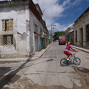 A local child rides her bike on the streets of Ceinfuegos, Cuba