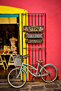 """SHOT 2/10/19 5:17:27 PM - A cruiser bike stands at the entrance to Los Bigotes de Frida, a boutique clothing store in the Los Sapos neighborhood of Puebla, Mexico.  Barrio de los Sapos, or Callejón de los Sapos (English: """"alley of the frogs""""), is a tourist attraction in the city of Puebla's historic center, in Puebla, Mexico. Puebla is the capital and largest city of the state of Puebla, and one of the five most important Spanish colonial cities in Mexico. A colonial era-planned city, it is located in southern Central Mexico on the main route between the capital, Mexico City, and Mexico's main Atlantic port, Veracruz. Being both the fourth largest city in Mexico and the fourth largest Metropolitan area in Mexico, it has a current population of 3,250,000 people, the city serves as one of the main hubs for eastern Central Mexico. The city also excels because of its industry including German automakers Volkswagen and Audi. (Photo by Marc Piscotty / © 2019)"""