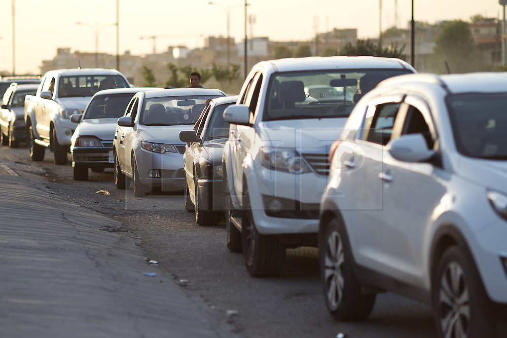 © Licensed to London News Pictures. 26/06/2014. Sulaimaniyah, Iraq. Iraqi drivers queue as they wait for a petrol station to receive a new shipment of fuel in Sulaimaniyah, Iraqi-Kurdistan. Despite being an oil-rich country Iraq's main oil refinery at Baiji is now the hands of ISIS insurgents cutting much of the fuel to the rest of the country. Petrol rationing has come in to force across northern Iraq with huge queues that mean many drivers wait in line for hours, sometimes overnight, just to receive their allowance of 30 litres. The shortage has also seen a huge increase in fuel prices with a litre of petrol rising 150% from 500 Iraqi Dinars to 1500 Iraqi Dinars. Photo credit: Matt Cetti-Roberts/LNP