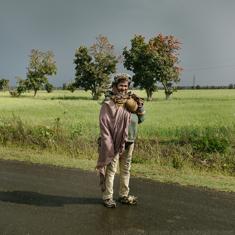 On a spiritual quest.<br /> I met him between two downpours. After the dryness of the cotton fields around Nagpur, it felt so good to see green wheat when entering Madhya Pradesh. I look back at the picture, and he reminds me so much of some of the hobos I met across the United States—a sack tied to a wooden stick, ripped jeans, and a sparkle in his eyes.<br /> Madhya Pradesh Province.