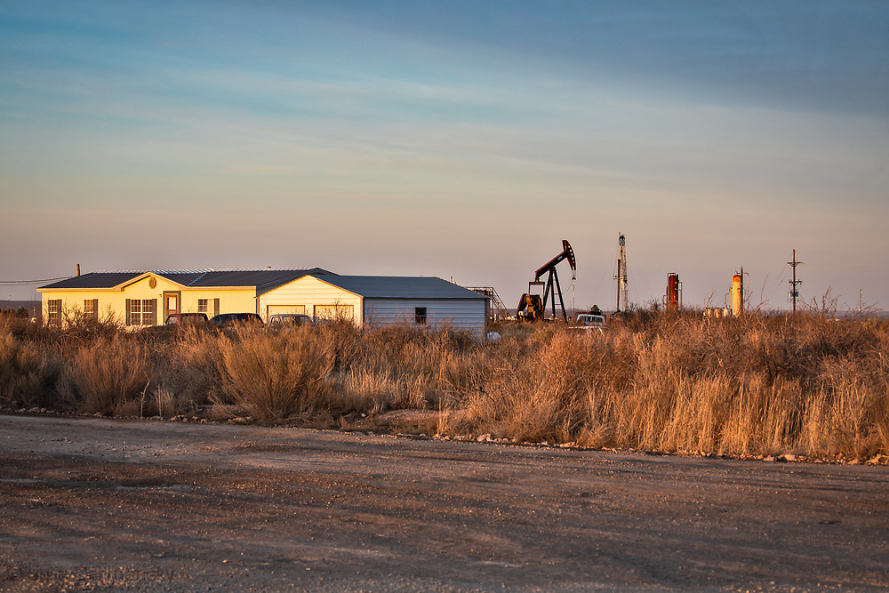 Home in the Permain Basin just south of Carlsbad New Mexico next to a pumpjack and a drilling rig.