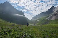 Female hiker hiking towards mountain pass on return from Horseid beach, Moskenesøy, Lofoten Islands, Norway