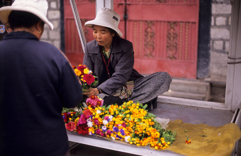 A woman sells flowers at Barkhor square, Lhasa, Tibet.