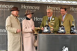 Left to right, TRISH & PETER ANDREWS owners of the 2015 Hennessy Gold Cup winner Smad Place receive the Hennessy Gold Cup from MAURICE HENNESSY and JO THORNTON at the 2015 Hennessy Gold Cup held at Newbury Racecourse, Berkshire on 28th November 2015.