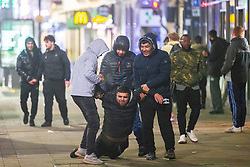 © Licensed to London News Pictures . 31/12/2020. Manchester, UK. Three men lift a fourth off the pavement in Piccadilly Gardens . The streets of Manchester stand nearly empty overnight (31st December 2020 to 1st January 2021) as Manchester enters the New Year under tier 4 of the government's Coronavirus lockdown . Photo credit: Joel Goodman/LNP
